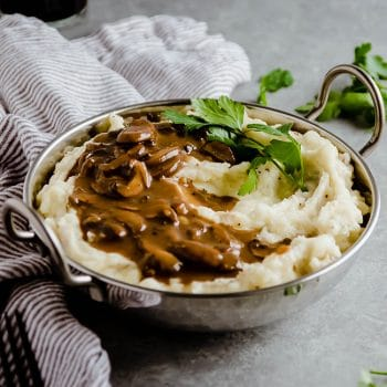 Metal dish filled with mashed potatoes and mushroom gravy on a grey background.