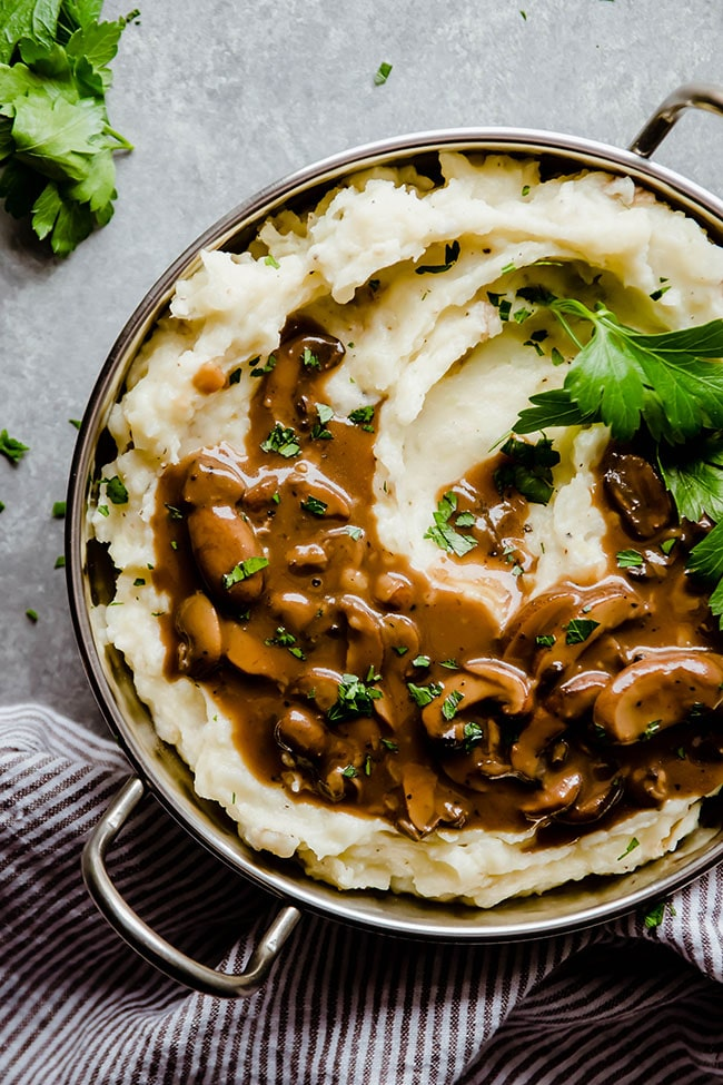 overhead photo of mashed potatoes topped with mushroom gravy and parsley in a metal pot
