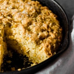 Cornbread in a cast iron skillet with one piece removed.