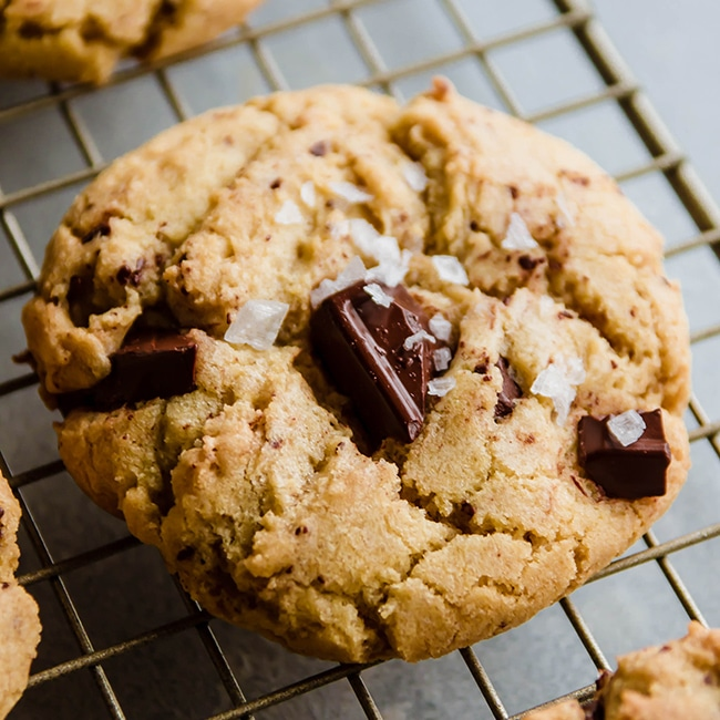 Chocolate chip cookie topped with sea salt sitting on a wire cooling rack