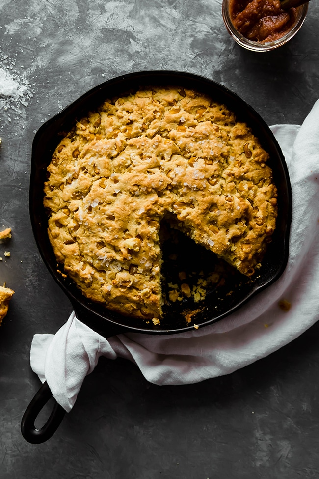 Overhead photo of cornbread in a cast iron skillet next to a linen napkin