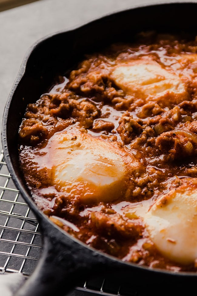 Baked eggs in a cast iron skillet with chorizo and tomato sauce.