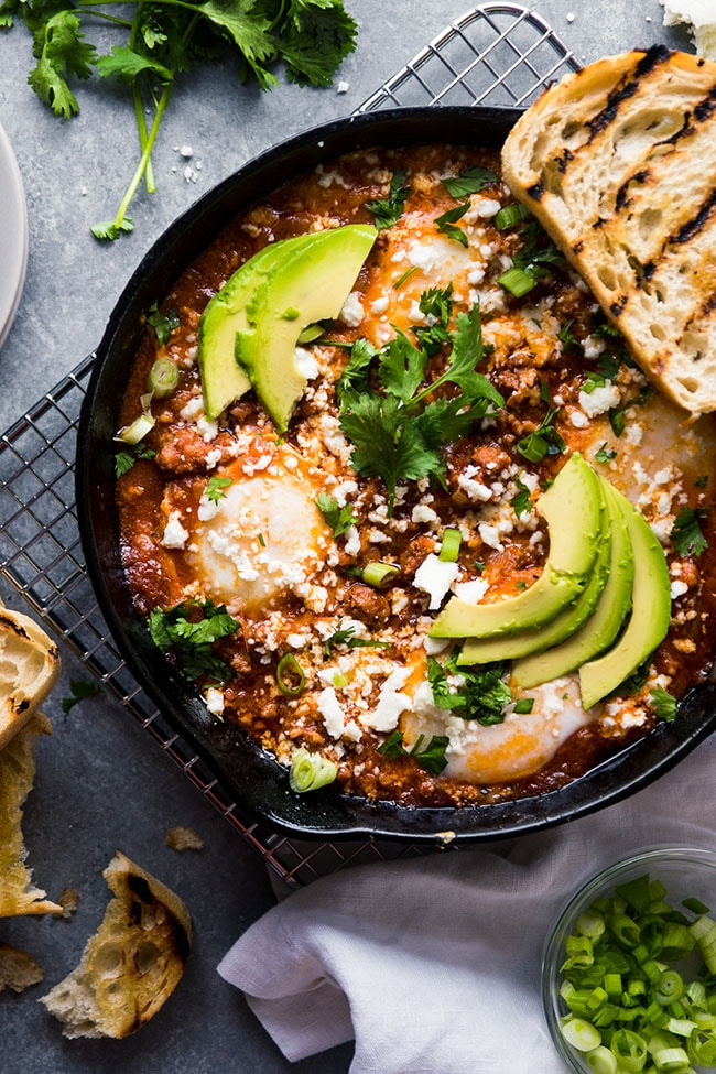 Baked eggs in tomato sauce, topped with avocado slices, fresh cilantro, and cotija cheese.