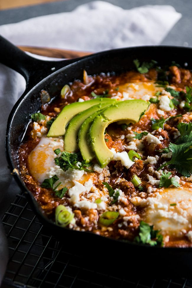 Baked eggs and tomato sauce in a skillet topped with avocado slices.