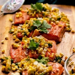 Four pieces of salmon topped with corn salsa on a wooden cutting board.