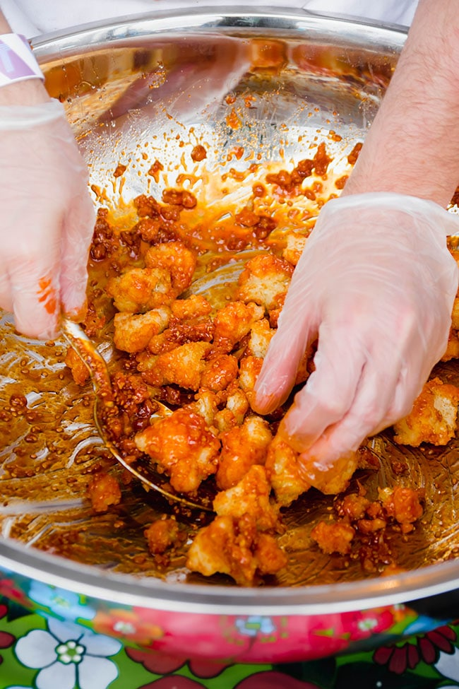 Hands mixing a bowl of fried cauliflower with buffalo sauce
