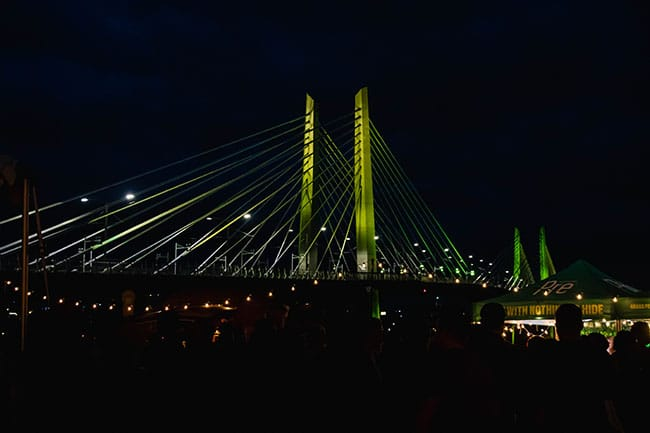 Tillikum Bridge lit up in the evening.