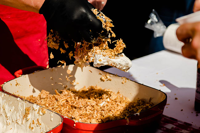 Bacon being coated with crispy breadcrumbs over a red baking dish.