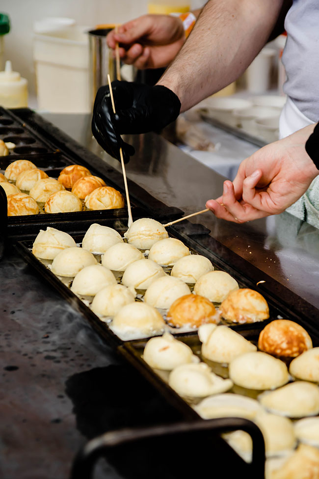 Hands flipping round pastries over a griddle.