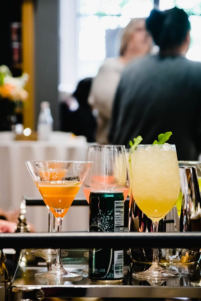 Multiple cocktails on a glass table.