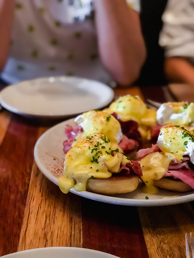 family style eggs benedict on a wood table
