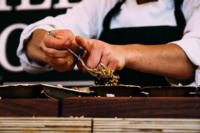 woman's hands putting bread crumbs over fresh pasta