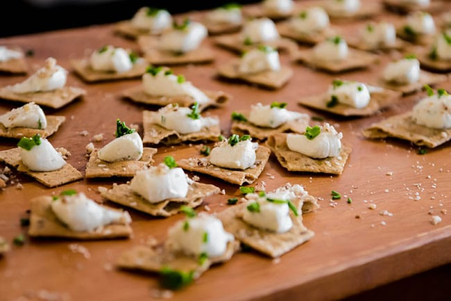 crackers topped with goat cheese and fresh herbs