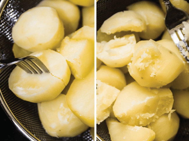 Cooked potatoes being pierced with a fork to test for doneness.