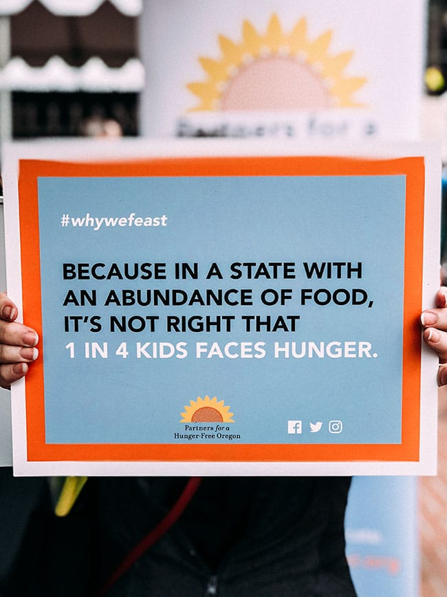 woman's hands holding a poster with hunger statistics at feast portland