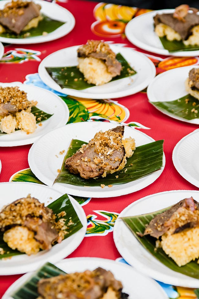 Appetizer bites of meat and rice on small white plates on a red floral tablecloth.