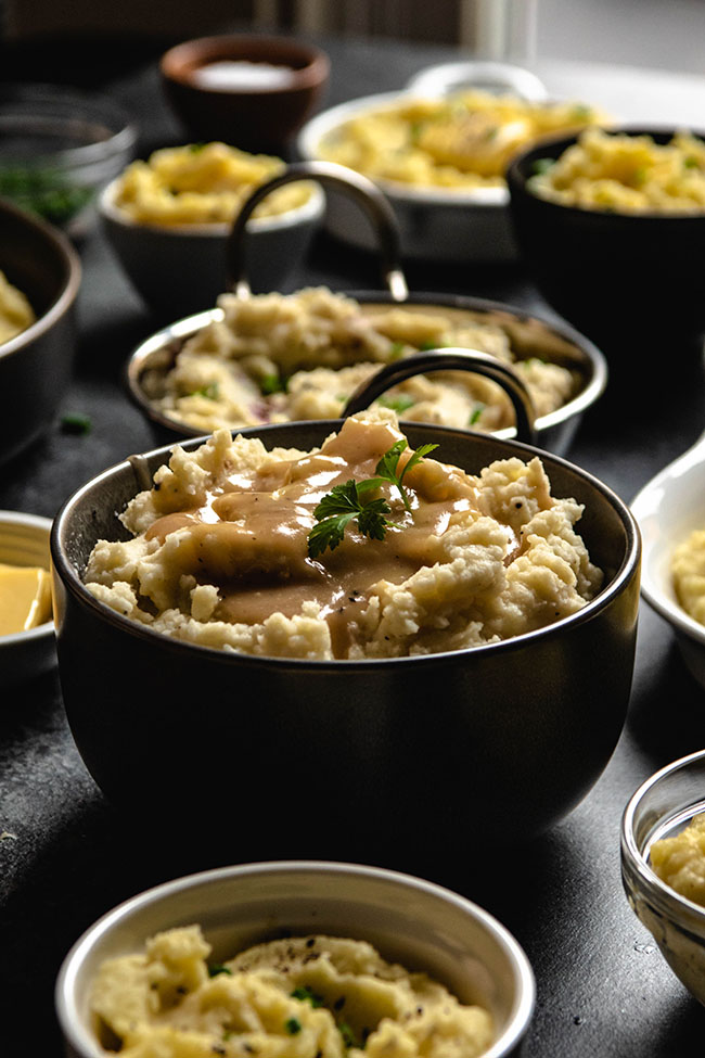 mashed potatoes with gravy and parsley in a black bowl surrounded by multiple small bowls of potatoes and toppings