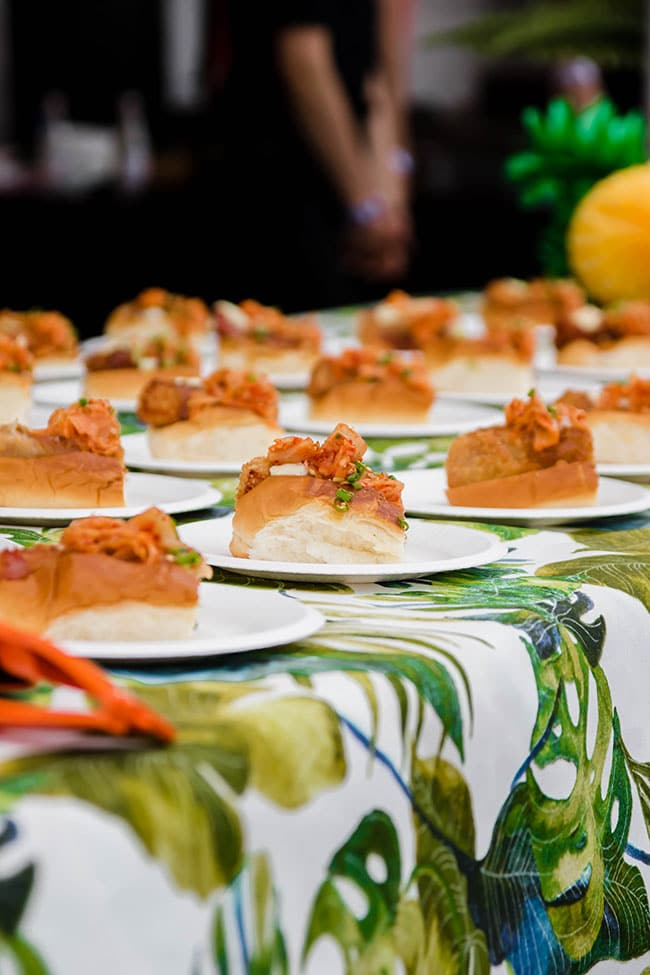 Lobster roll appetizers on individual plates on a floral print tablecloth.