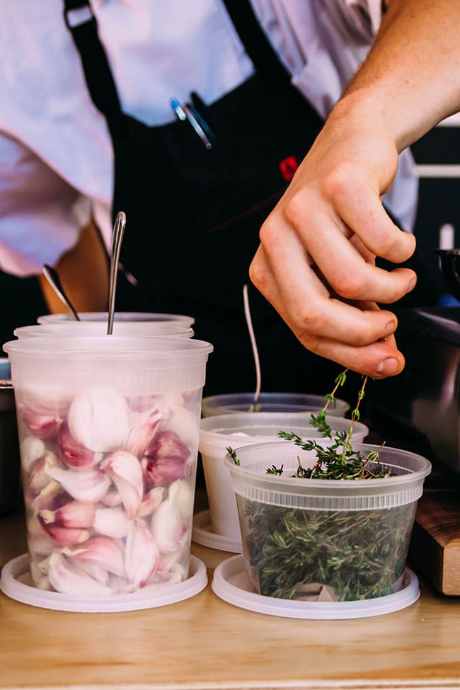 man's hand pulling sprigs of thyme out of a plastic container