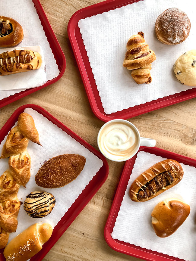 overhead photo of four red trays full of pastries