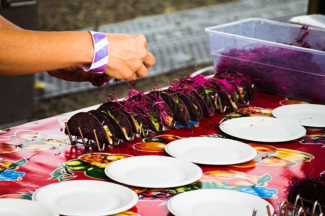 woman's hand putting a garnish on a row of tacos with purple shells
