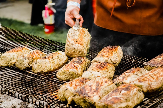 Man\'s hands using tongs to flip pork rounds over on a large grill.