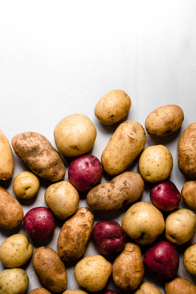 overhead photo of multiple whole potatoes in varying colors on a white background
