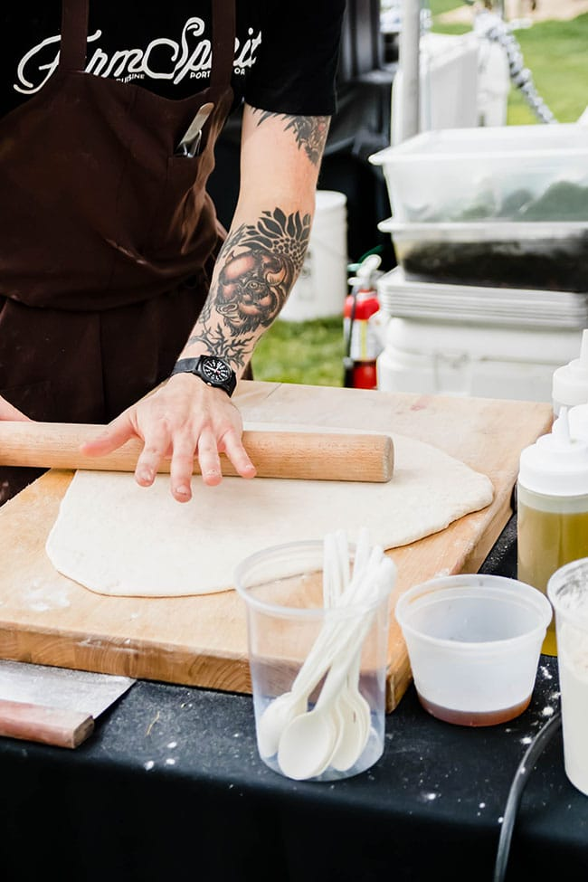 Man\'s hands rolling pizza dough into a circle with a wood rolling pin.