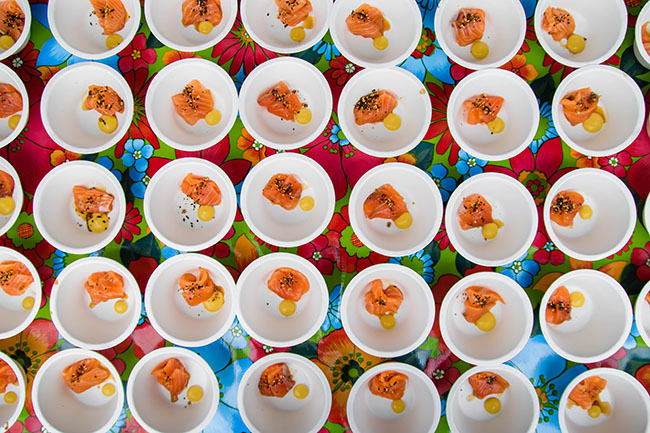 Overhead photo of dozens of small white bowls filled with pieces of sliced raw salmon