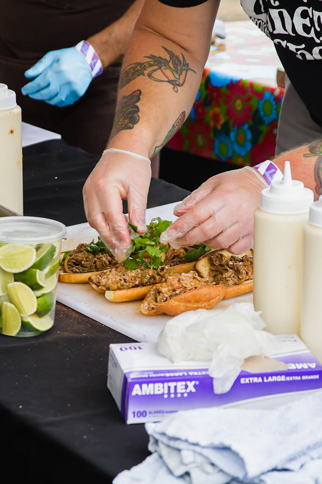 Man\'s hands assembling two banh mi sandwiches on a black prep table surrounded by ingredients.