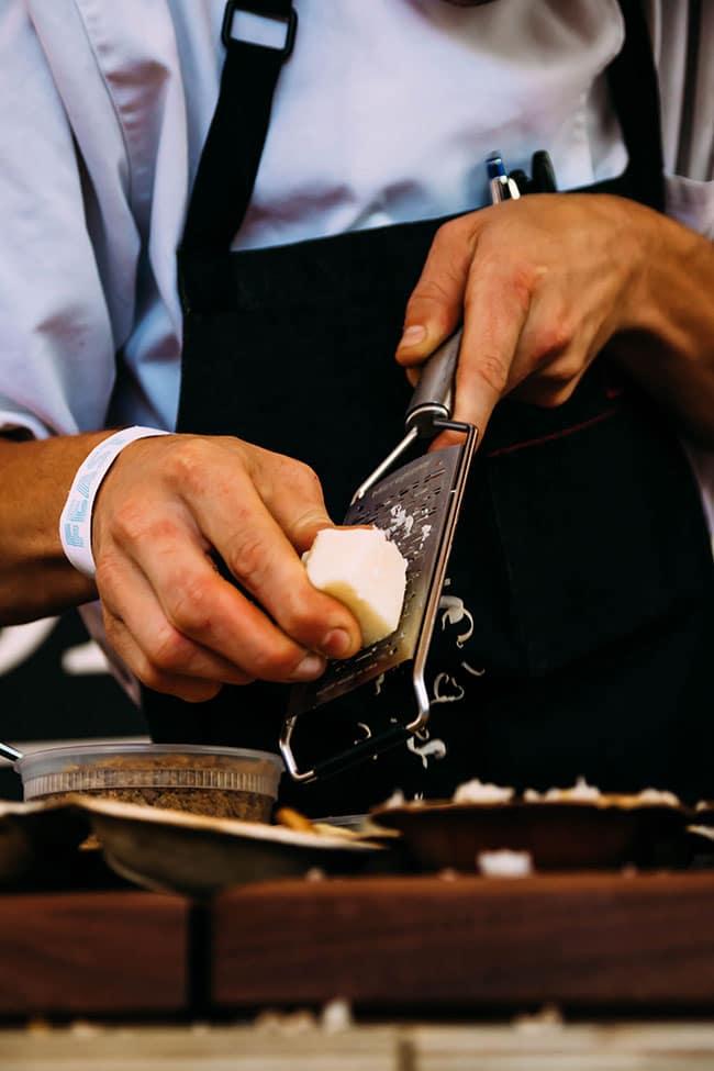 man's hands shredding parmesan cheese over fresh pasta