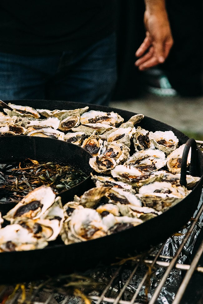 Oysters in a black cast iron pan being smoked over a large fire.