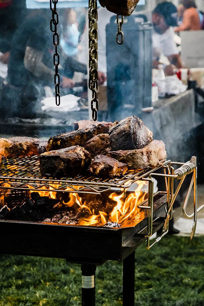 Meat smoking on a large grill over an open flame.