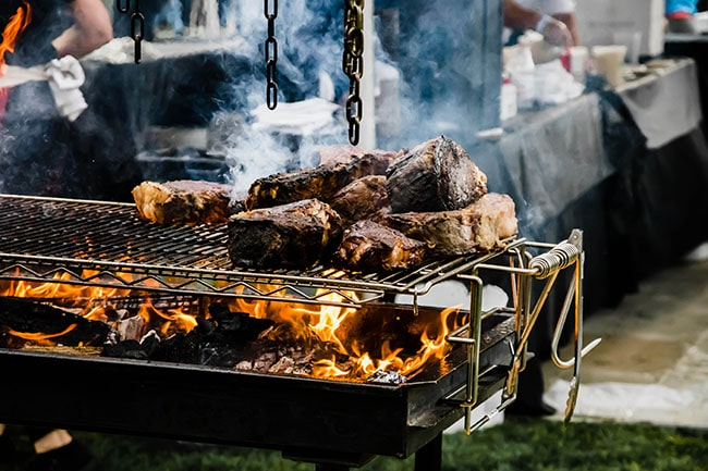 Slabs of meat cooking on a grate over an open flame.