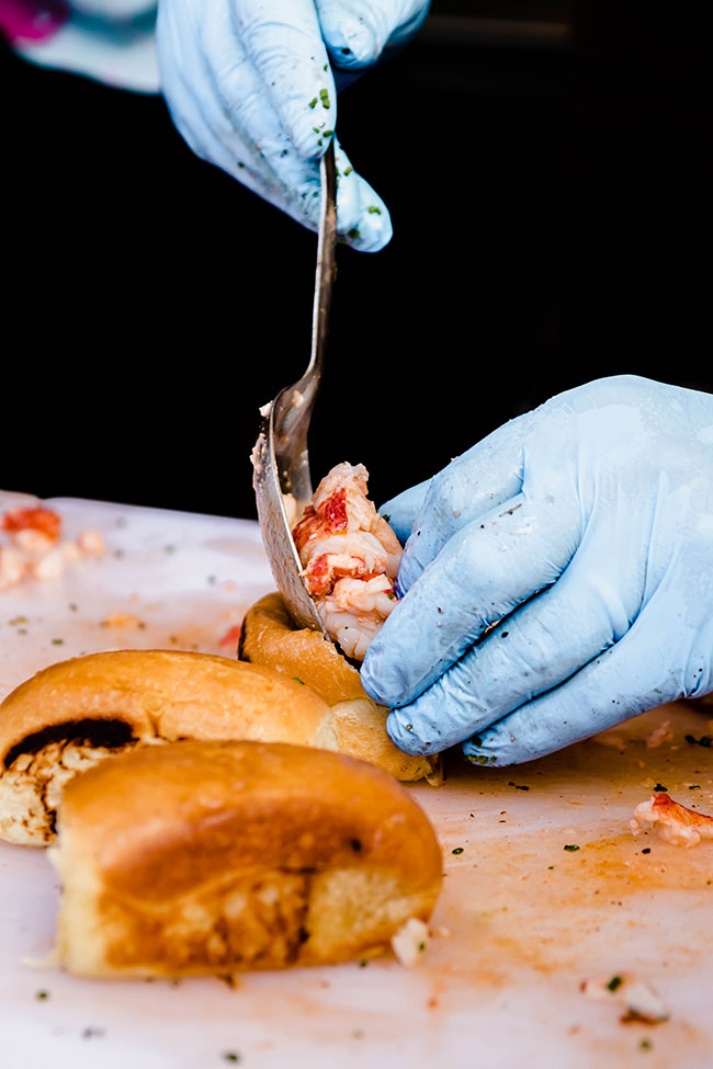 hands in blue gloves stuffing lobster into a small roll