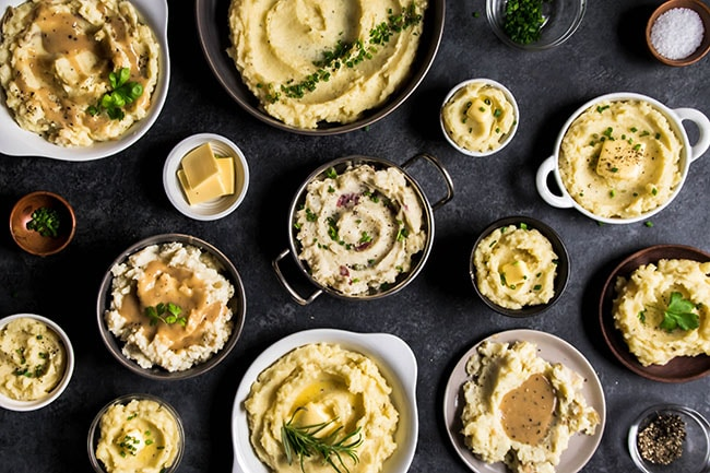 Overhead photo of multi-colored bowls filled with mashed potatoes and a variety of toppings on a black background