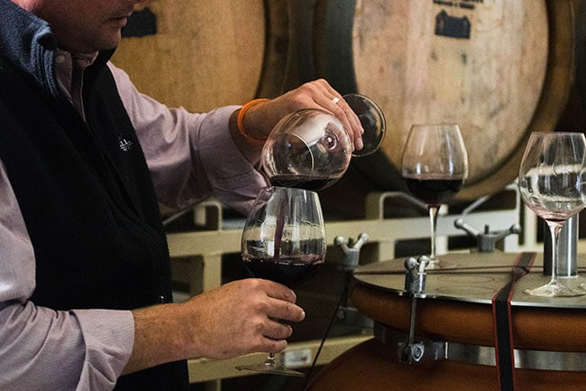 man's hands pouring wine from one glass into another glass