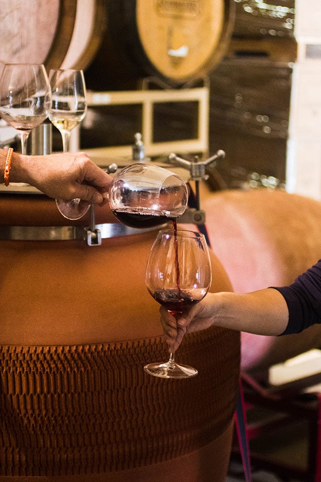 man's hand pouring wine out of a wine glass into another wine glass