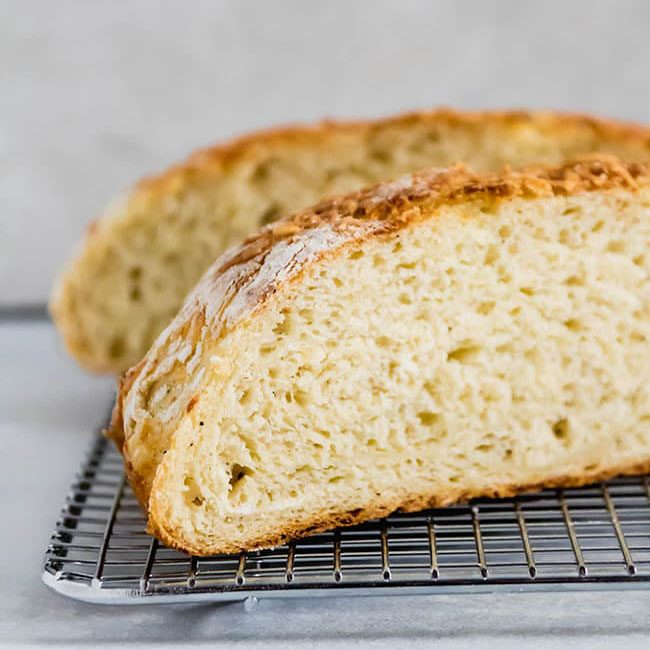 two halves of a loaf of bread on a cooling rack in front of a white background