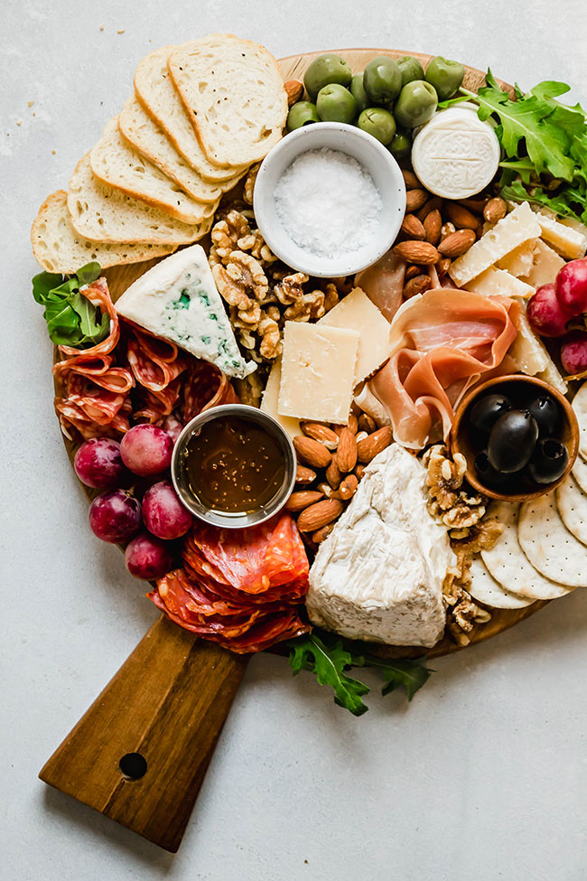Cheese and charcuterie on a round wooden cutting board on a white table.