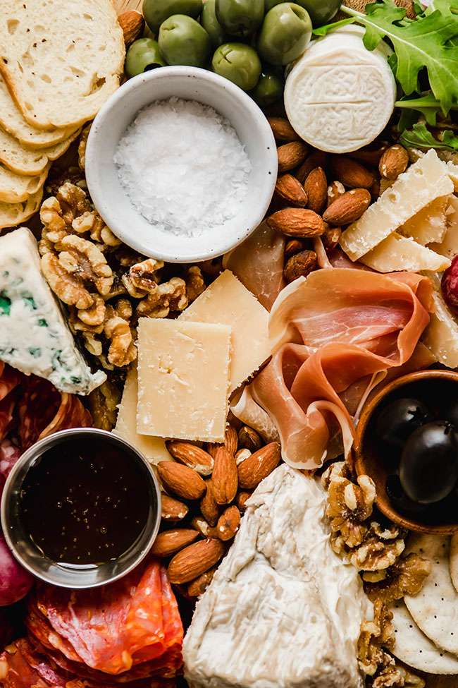 Close up of a cheese plate filled with nuts, cheeses, charcuterie, and olives.