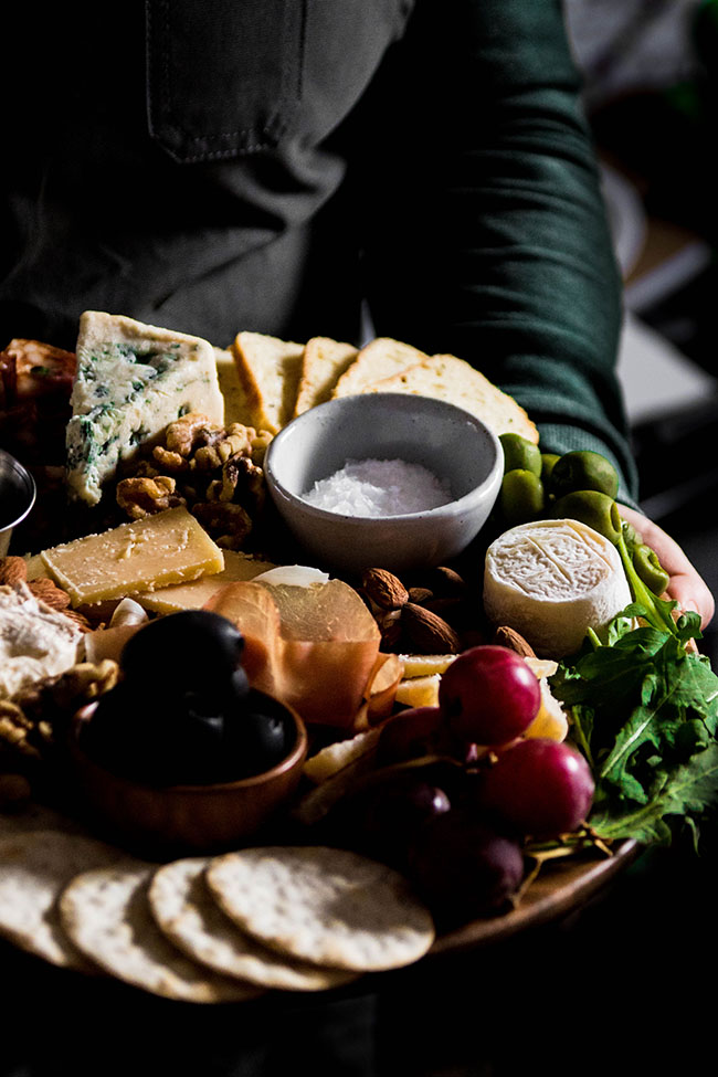 Woman in a green shirt holding a cheese board with goat cheese, grapes, black olives, and blue cheese.
