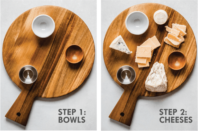 Round wooden board with three small empty bowls and a variety of cheeses. Grey text overlay says \'step 1: bowls, step 2: cheeses.\'