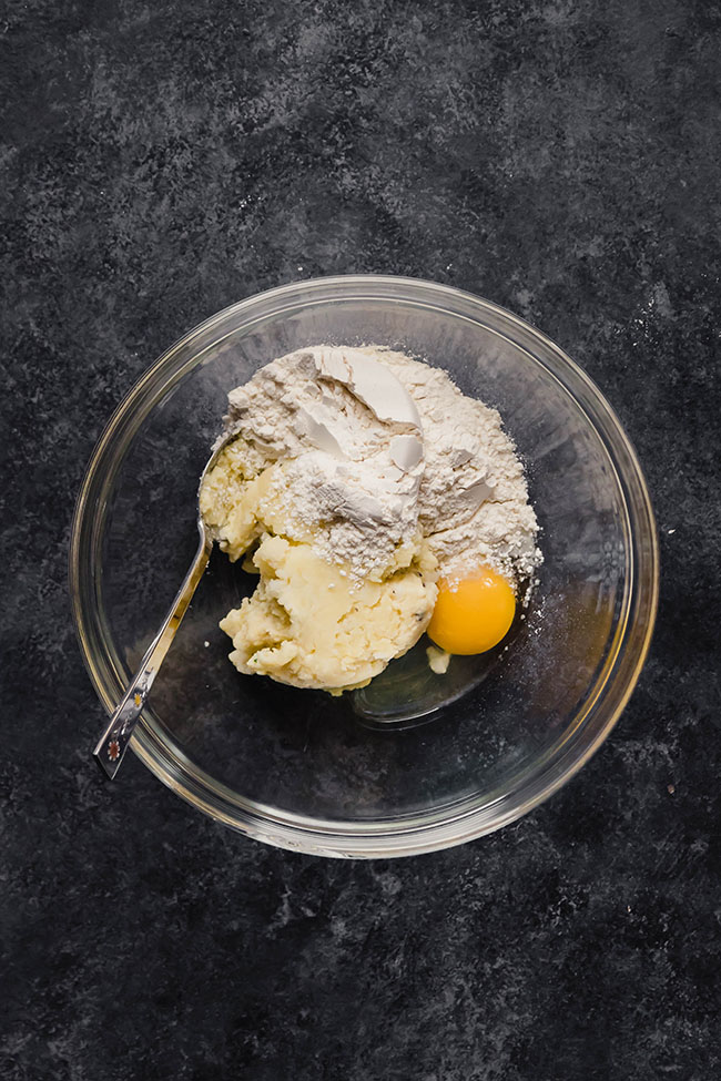 overhead photo of mashed potatoes, flour, and an egg in a glass bowl on a black countertop