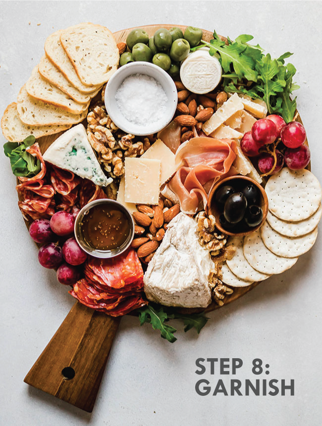 A completed cheese plate with fresh arugula tucked around the edges. Grey text overlay says \'step 8: garnish.\'