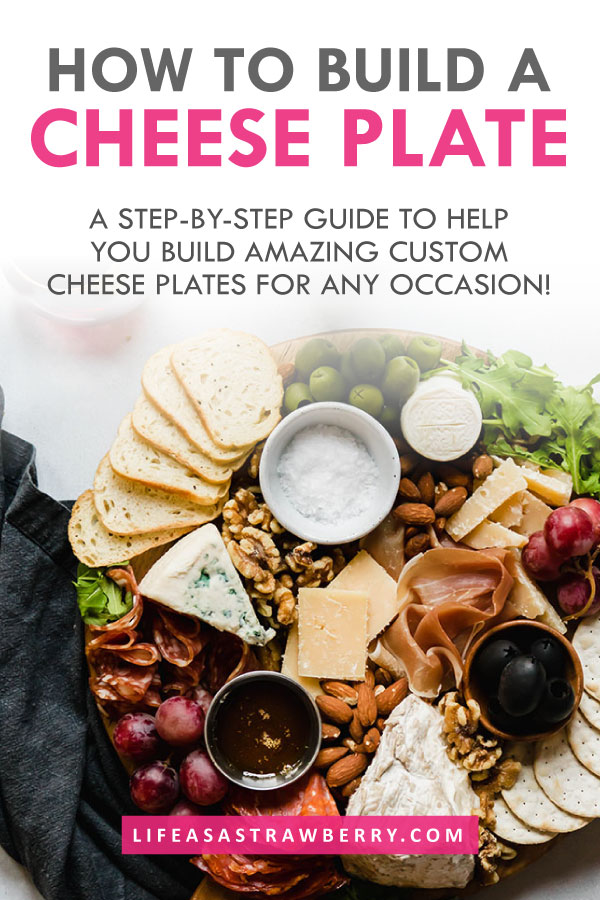 """overhead photo of a cheese and charcuterie platter with text overlay that reads """"how to build a cheese plate"""" in grey and pink text"""