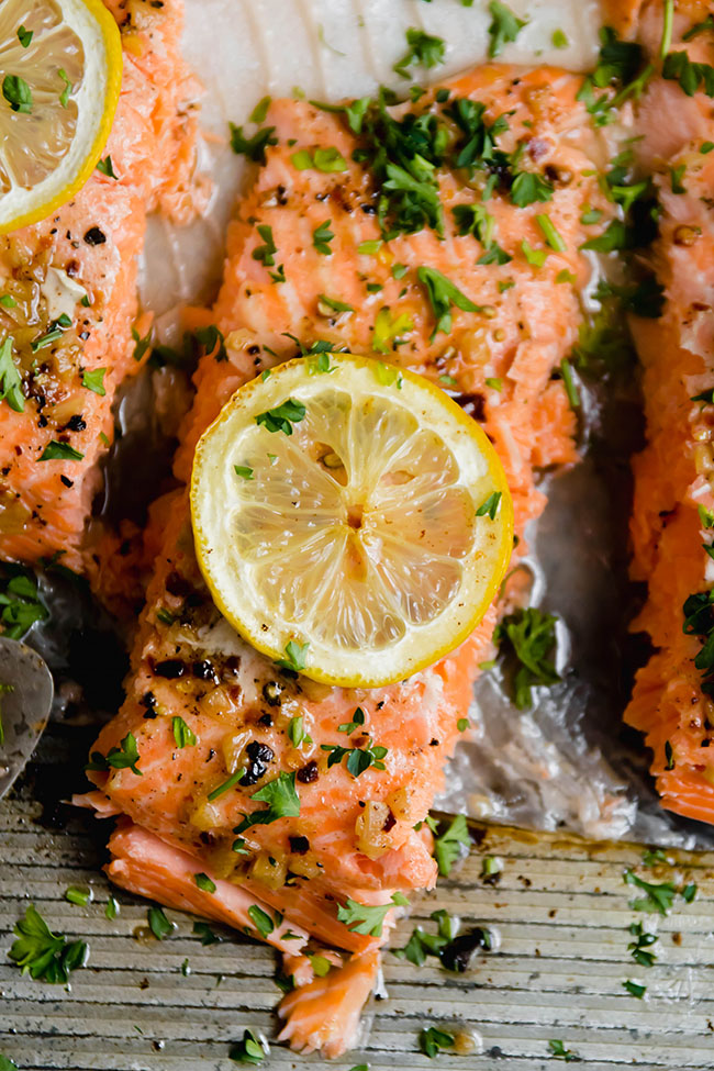 Baked steelhead trout portions topped with parsley and lemon slices.