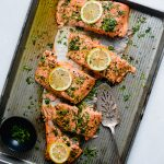 overhead photo of baked steelhead fillet on a metal sheet pan, topped with fresh parsley and lemon slices and cut into portions