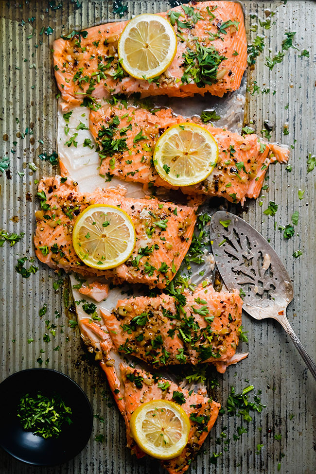 Steelhead trout fillet topped with lemon and parsley and cut into slices.
