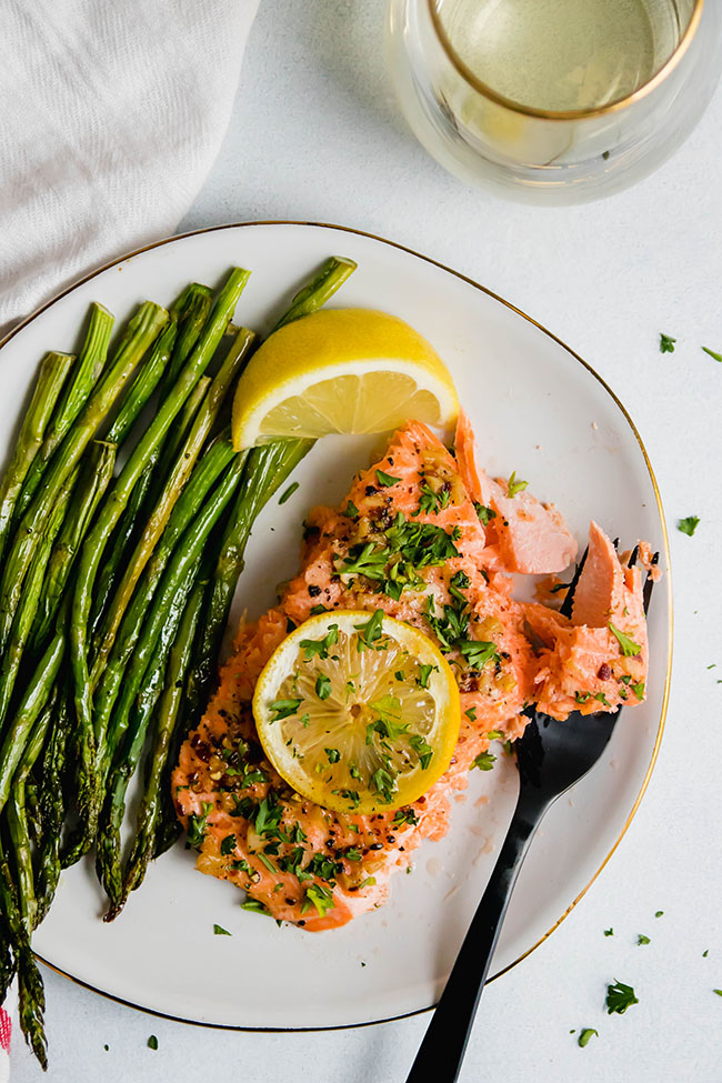 Roasted steelhead topped with lemon slice and parsley on a white plate with roasted asparagus.